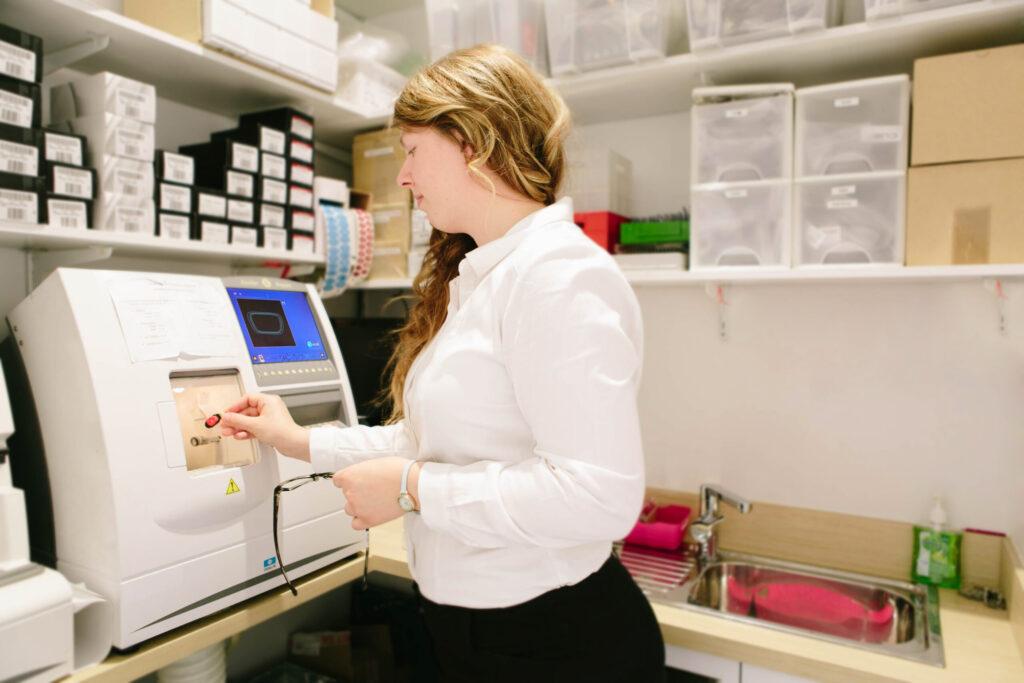 Girl using an edger to cut lens in an optical lab