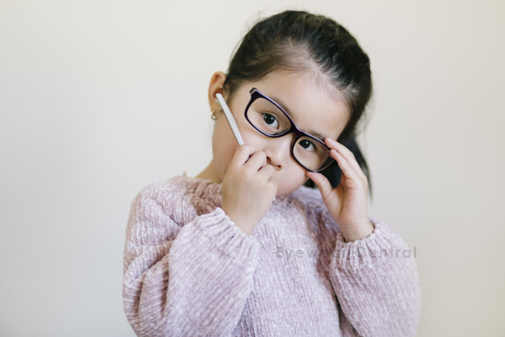 Child wearing a broken glasses. Her hand holding the frame arm that came off