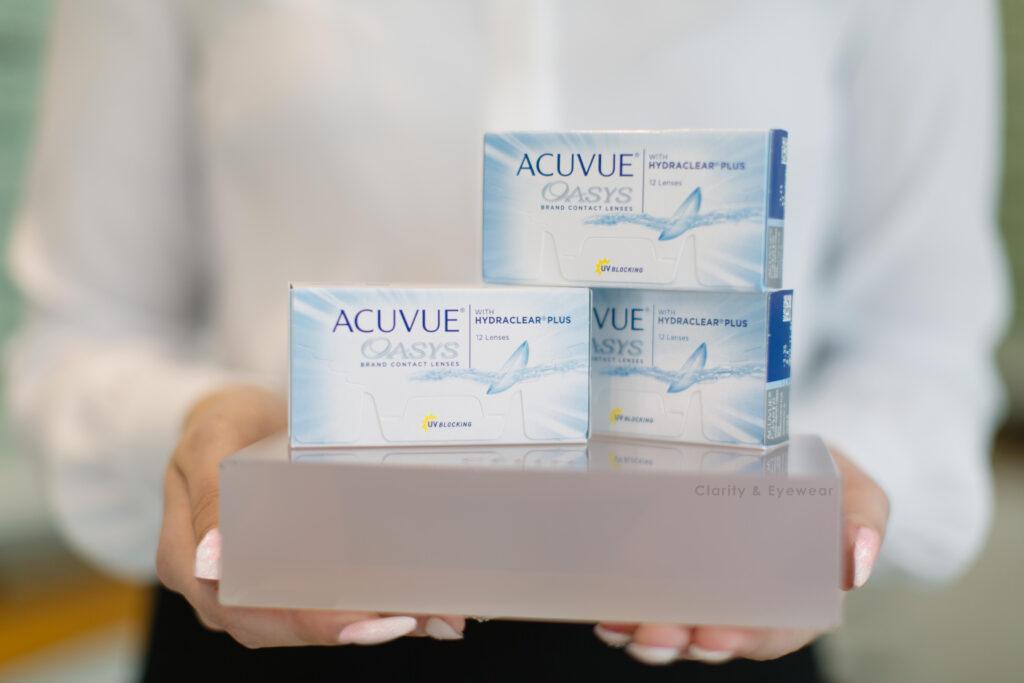 person holding 3 boxes of Acuvue Contact lenses