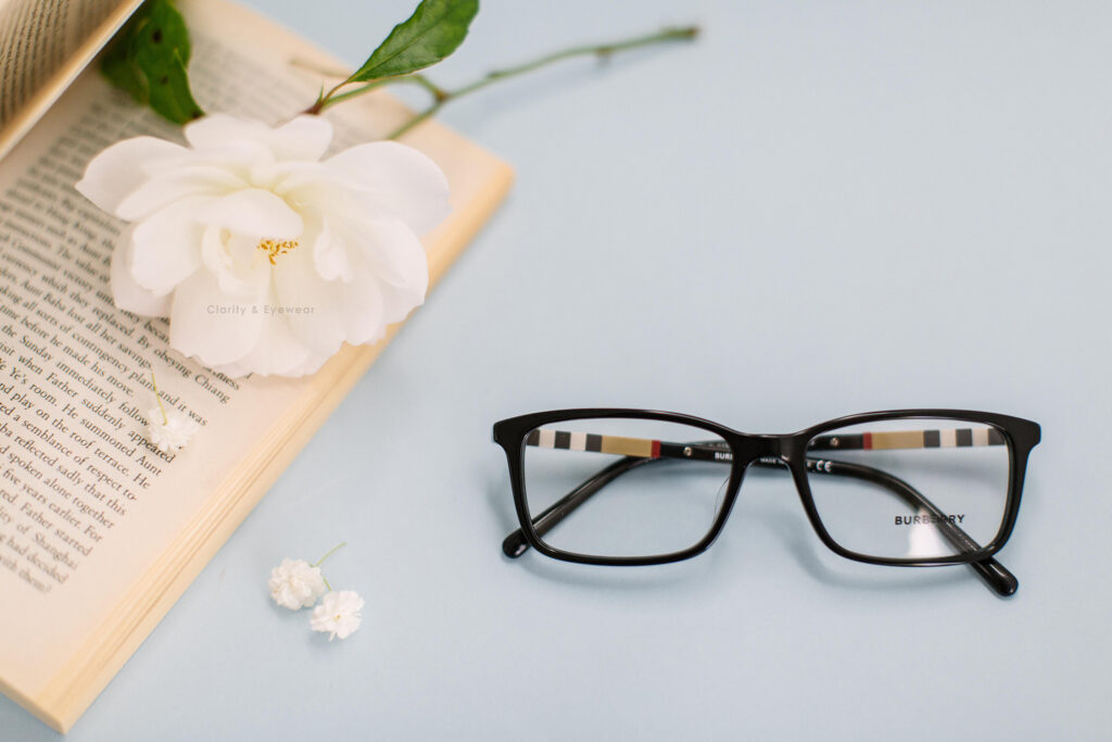 black burberry squarish frame with a book and flower