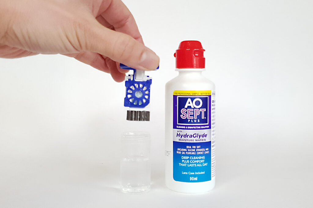 A hand inserting the OrthoK lenses inside its case with a bottle of AO Sept next to it