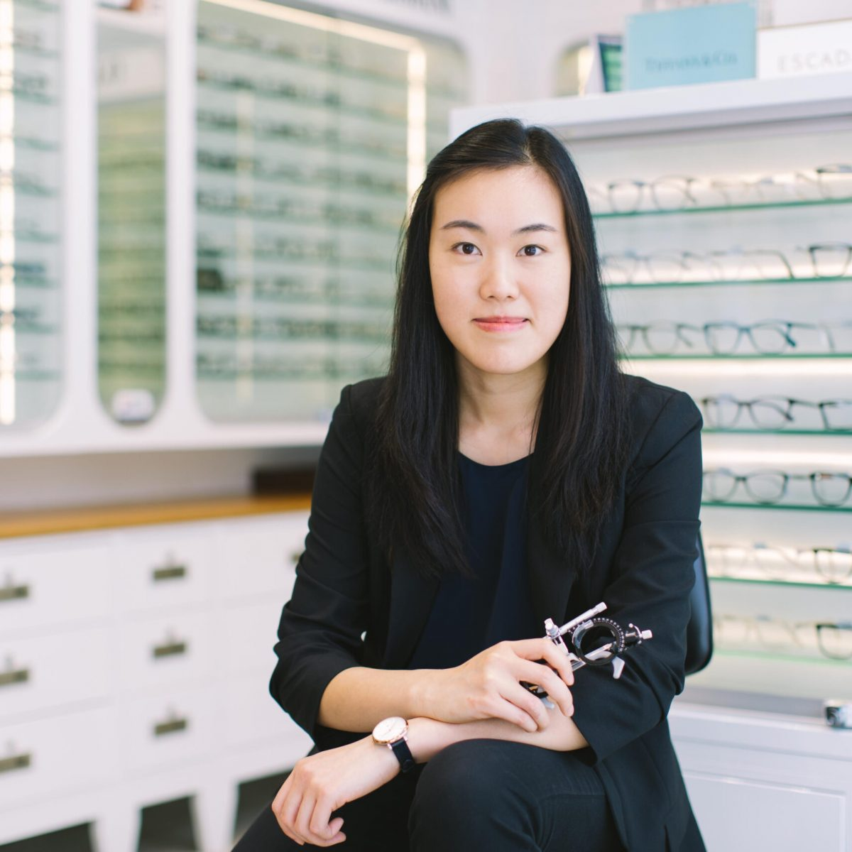 Dr. Sylvia Chau optometrist holding a trial frame