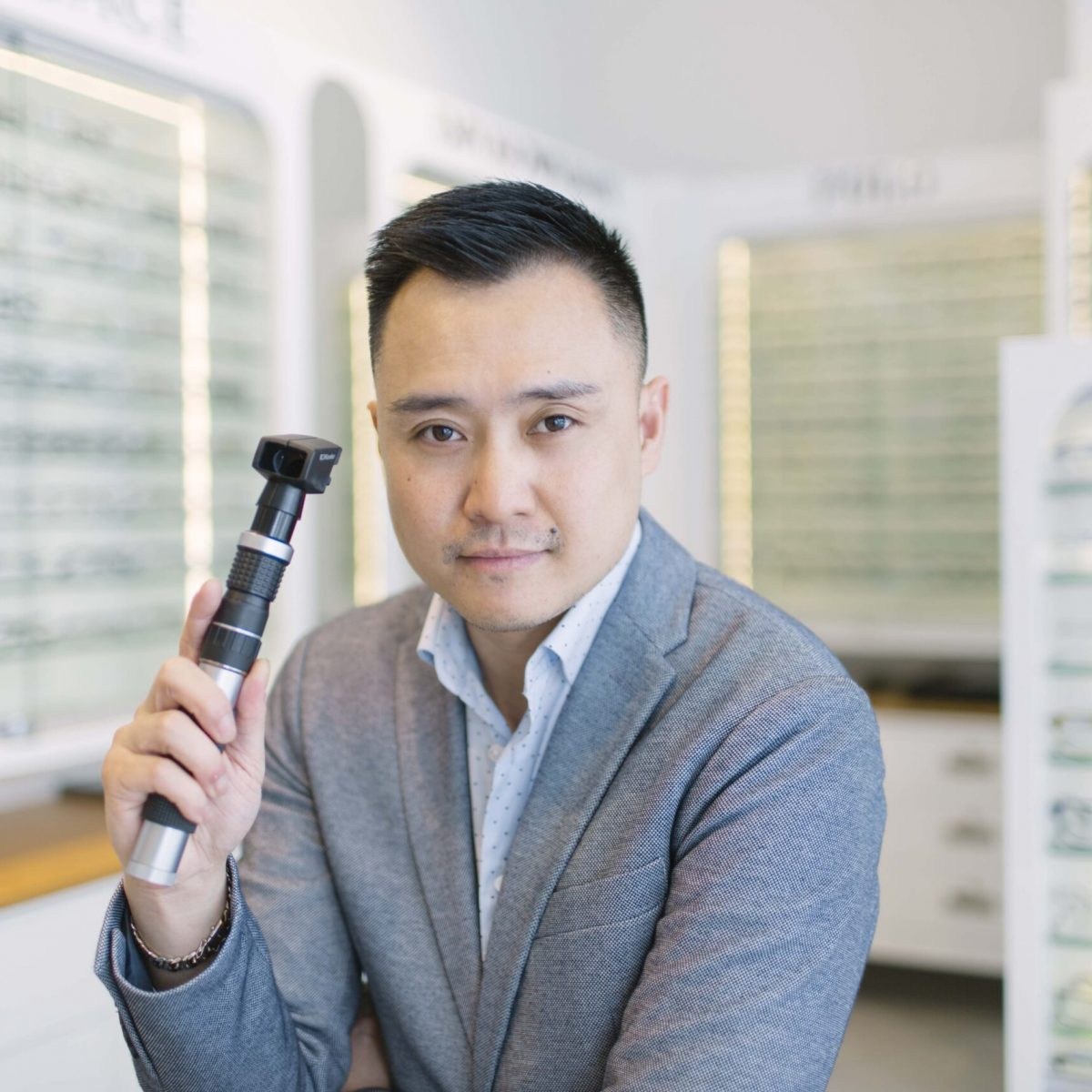 Dr. Peter Le optometrist holding a scope